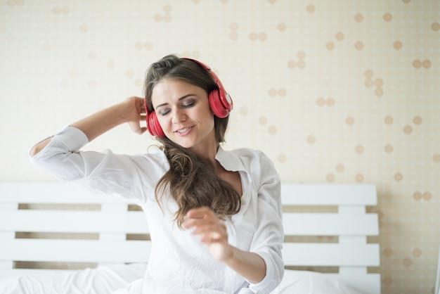 Música que escucha de la mujer hermosa en la mañana que se sienta en cama en casa Foto gratis