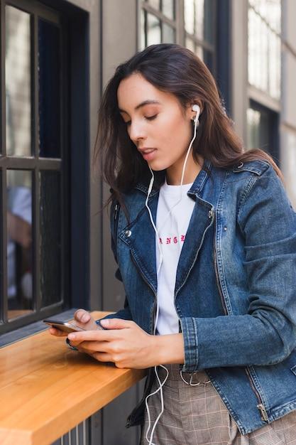 Música que escucha de la mujer joven en el auricular usando smartphone Foto gratis