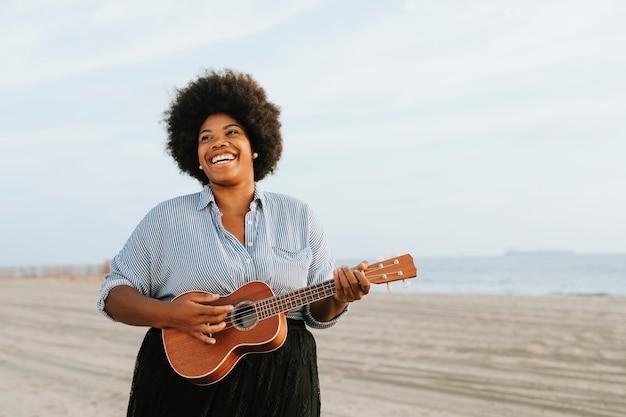 Músico afroamericano tocando el ukelele en la playa Foto gratis