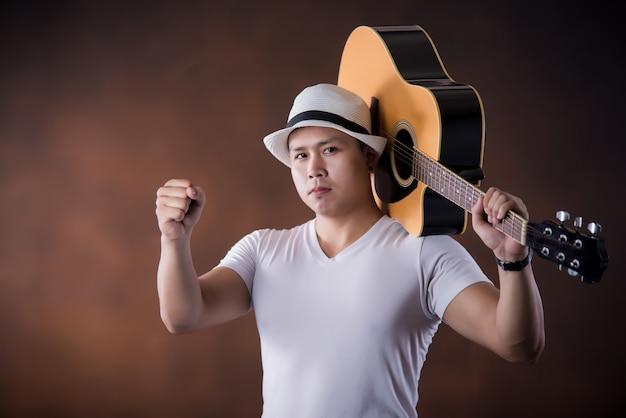 Músico joven asiático con guitarra acústica Foto gratis