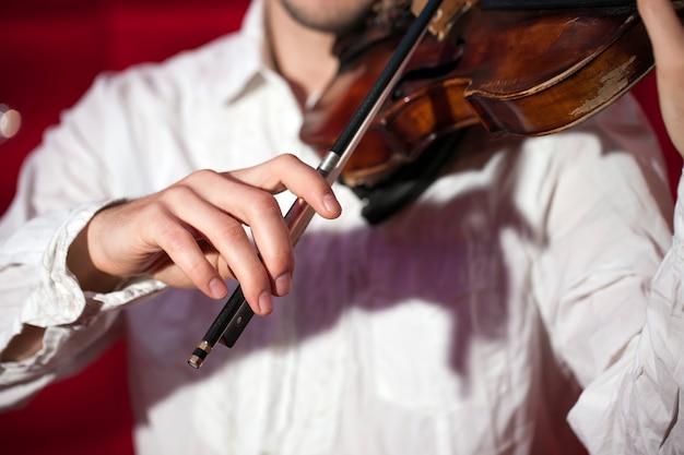 Músico joven que toca el violín en un restaurante en una pared roja. Foto Premium