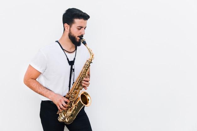 Músico de tiro medio tocando el saxofón. Foto gratis