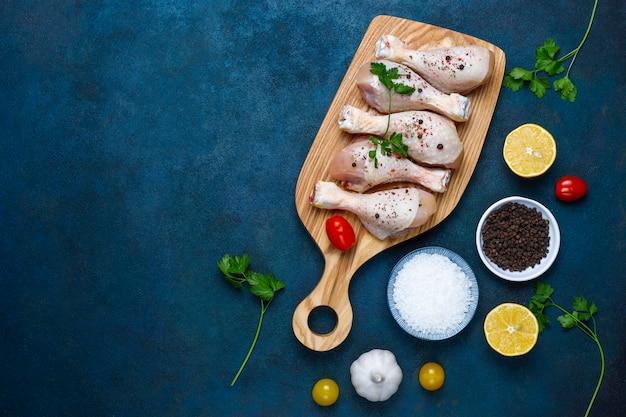 Muslos de pollo con especias y sal listos para cocinar en la tabla de cortar. Foto Premium