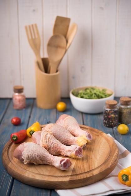 Muslos de pollo sobre tabla de madera con pimientos Foto gratis