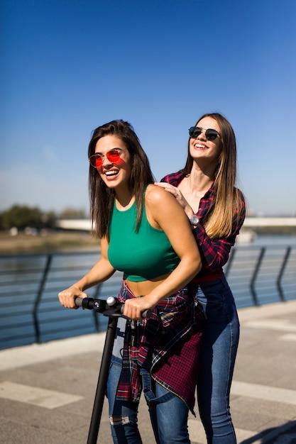 Muy jóvenes amigas montando un scooter eléctrico en la calle Foto Premium