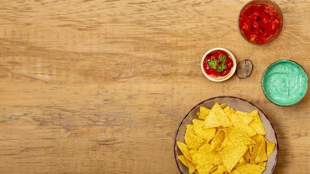 Nachos y diferentes salsas orgánicas en mesa de madera Foto gratis