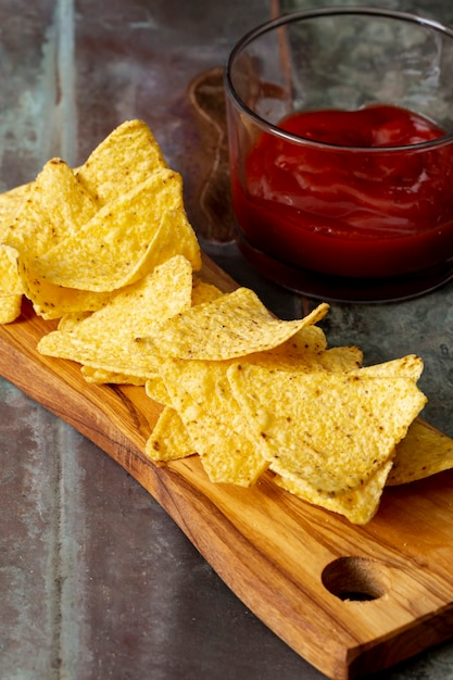 Nachos en tabla de cortar y salsa de tomate en recipiente de vidrio Foto gratis
