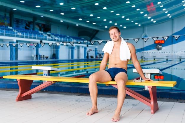 Nadador de tiro largo posando con una toalla sobre sus hombros Foto gratis