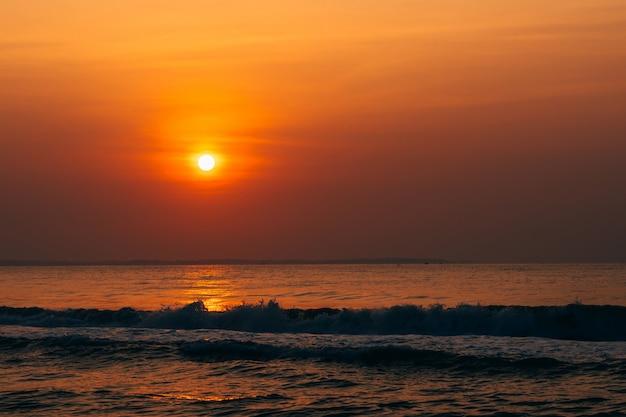 Naranja amanecer contra el mar con olas Foto Premium