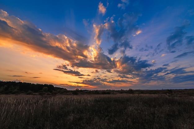 Naranja puesta de sol azul con rayos de sol a través de las nubes en el cielo en el campo en la noche Foto Premium