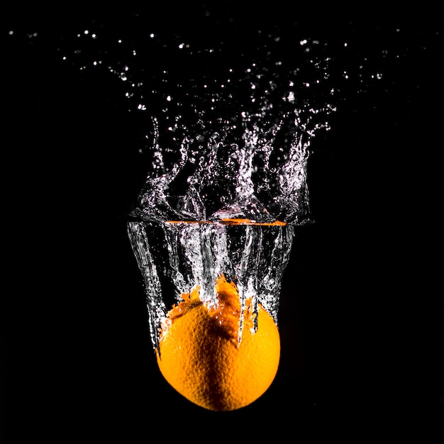Naranja sumergiéndose en el agua Foto gratis