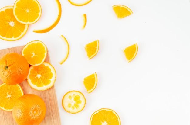 Naranjas esparcidas sobre tabla de cortar y mesa Foto gratis