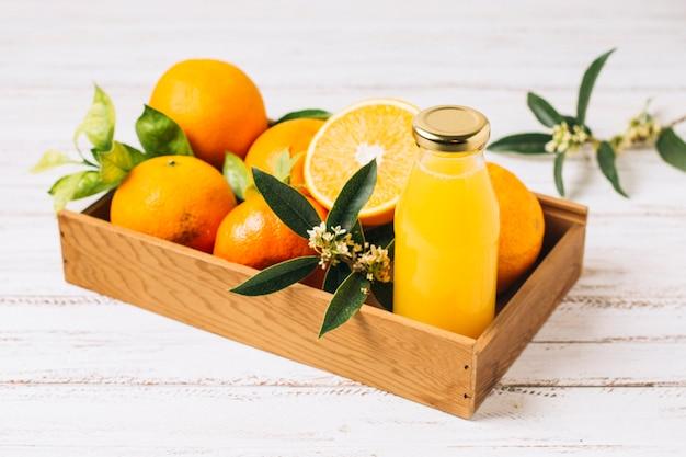 Naranjas y zumo en caja de madera. Foto gratis