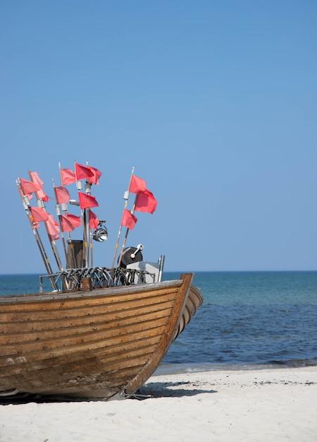 Nariz de barco de pesca en una playa de arena con varias pequeñas banderas rojas en astas de bandera Foto Premium