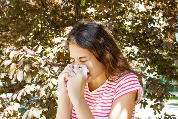 Nariz que sopla de la muchacha bonita joven delante del árbol. concepto de alergia de primavera Foto Premium