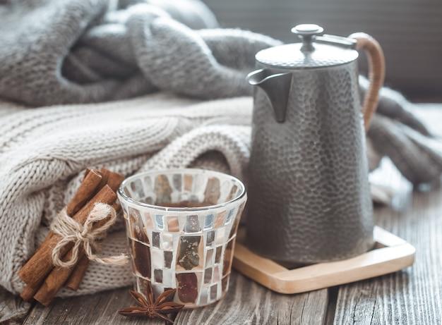 Naturaleza muerta con artículos de decoración para el hogar, teteras y un vaso de té en una mesa de madera en el interior de la sala de estar, concepto hogareño Foto Premium