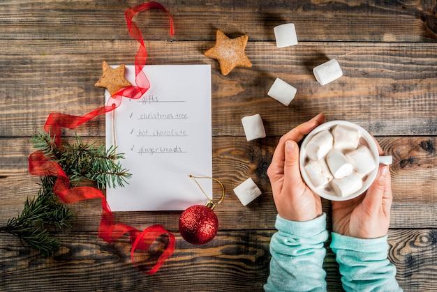 Navidad, año nuevo concepto. mesa de madera, cuaderno con lista de tareas, las manos de la niña sostiene la taza de cacao, la bola de navidad, el pino, la cinta roja, el malvavisco vista superior copyspace Foto Premium