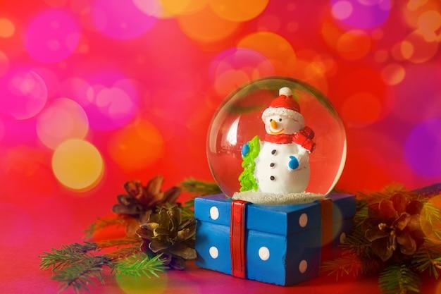 Navidad y año nuevo muñeco de nieve globo de nieve interior sobre fondo rojo bokeh Foto Premium
