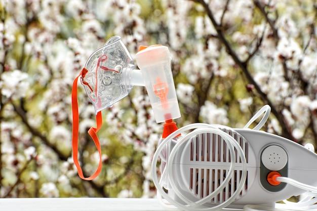 Nebulizador con una máscara en árbol floreciente. Foto Premium