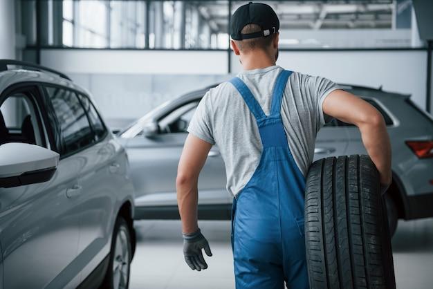 Esto necesita ser eliminado. mecánico sosteniendo un neumático en el taller de reparación. reemplazo de neumáticos de invierno y verano. Foto gratis