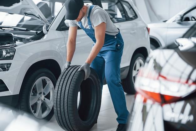 Necesito darme prisa. mecánico sosteniendo un neumático en el taller de reparación. reemplazo de neumáticos de invierno y verano Foto gratis