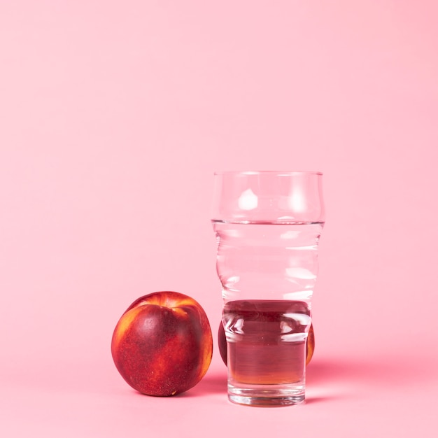 Nectarina y agua sobre fondo rosa Foto gratis