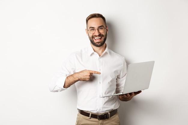 Negocio. gerente guapo en gafas trabajando en equipo portátil, apuntando a la computadora y sonriendo complacido, de pie Foto gratis
