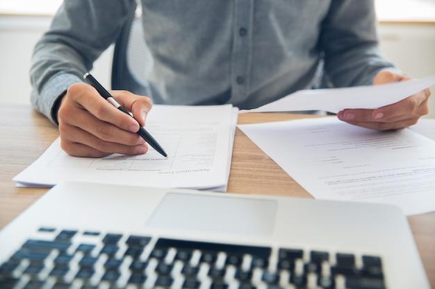 De negocios que controla los documentos en la mesa Foto gratis