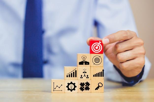 Los negocios sostienen un objetivo con flecha, apilando bloques de madera en escalones Foto Premium