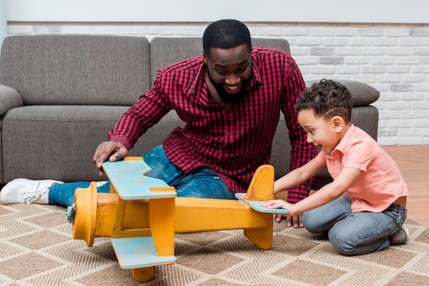 Negro padre e hijo jugando con avión de juguete Foto gratis