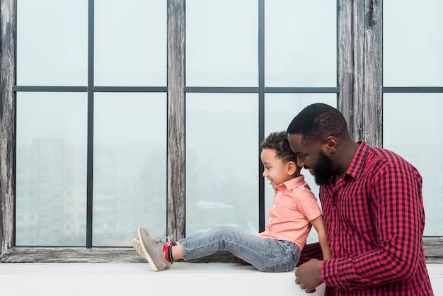 Negro padre e hijo de pie en el alféizar de la ventana Foto gratis