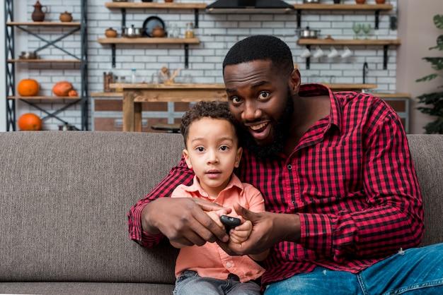 Negro padre e hijo viendo television Foto gratis