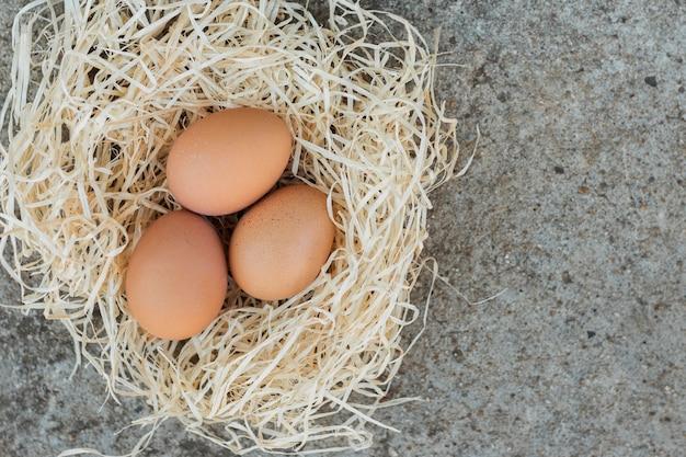 Nido blanco lleno de huevos marrones Foto gratis
