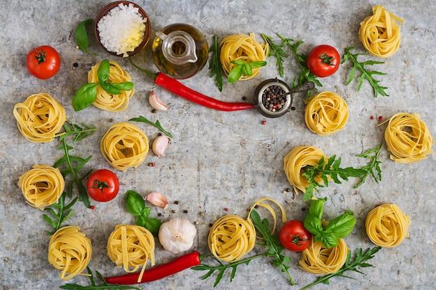 Nido de tallarines de pasta e ingredientes para cocinar (tomates, ajo, albahaca, chile). vista superior Foto gratis