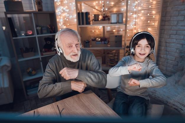 Nieto y abuelo escuchando auriculares de música Foto Premium