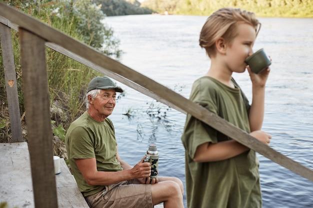 Nieto y abuelo yendo a pescar al río Foto gratis