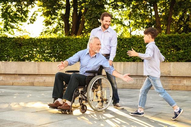 Nieto ven al pensionista siéntate en silla de ruedas. Foto Premium