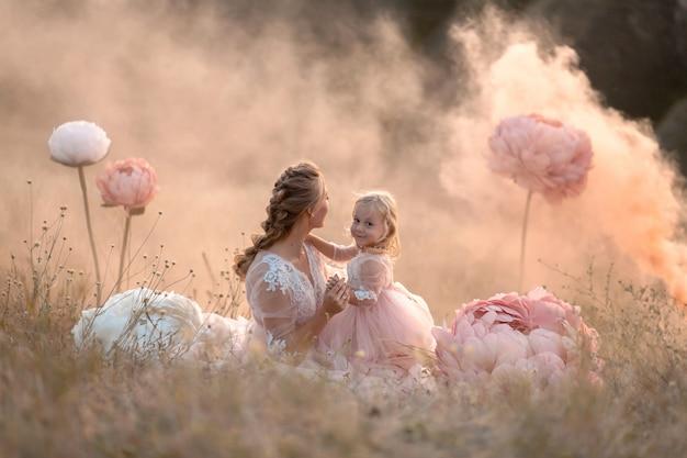 Una niña abraza a su madre sentada en un campo rodeado de grandes flores decorativas rosadas irreales Foto Premium