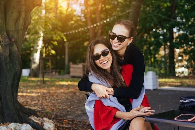 Niña abrazando a su amiga. retrato dos novias en el parque. Foto gratis