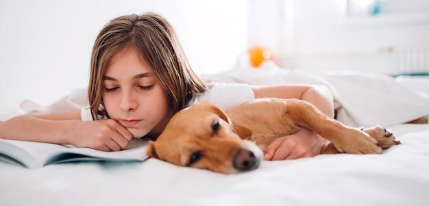Niña acostada en la cama con su perro y libro de lectura Foto Premium