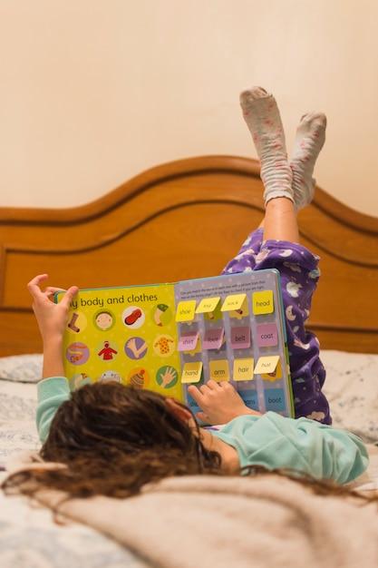Niña acostada en la cama leyendo el libro de texto   Descargar Fotos ...