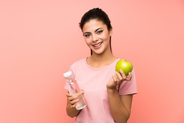 Niña adolescente feliz sobre pared rosa aislado con una botella de agua y una manzana Foto Premium
