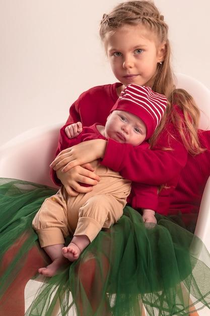 Niña adolescente feliz con su hermanita bebé recién nacido. amor familiar. Foto gratis