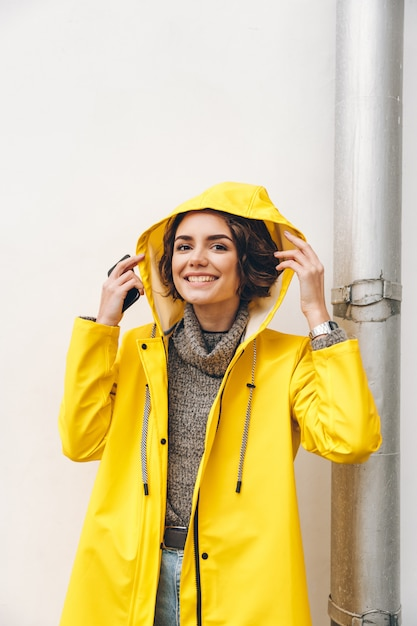 Niña adulta sonriente en capa amarilla poniendo capucha en la cabeza posando en cámara con sincera sonrisa ser feliz Foto gratis