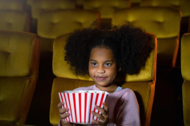 La niña africana está sentada y viendo el cine en los asientos de las salas de cine. las caras se sienten felices y disfrutan. Foto Premium