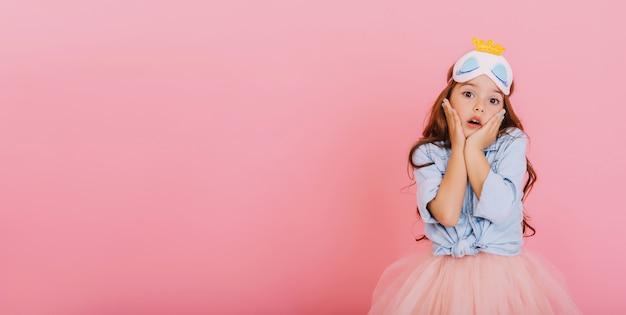 Niña alegre con cabello largo morena en máscara de princesa mirando asombrado a la cámara aislada sobre fondo rosa. celebrando el carnaval brillante para niños, divirtiéndose. lugar para el texto Foto gratis