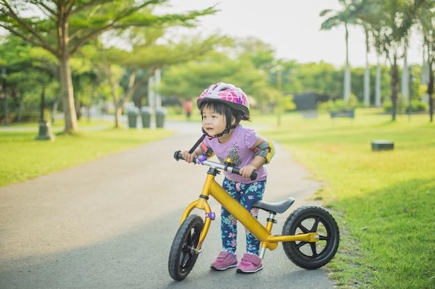 Niña Montando Su Bicicleta En Un Parque: Niña Aprende A Montar Bicicleta De Equilibrio En El