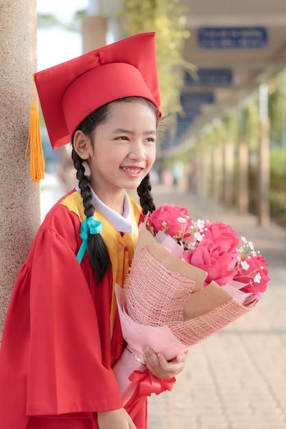 Niña asiática en vestido rojo graduado de sonrisa con felicidad ...
