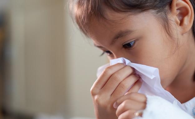 Niña asiática enferma limpiando y limpiando la nariz con pañuelos en la mano en el hospital Foto Premium