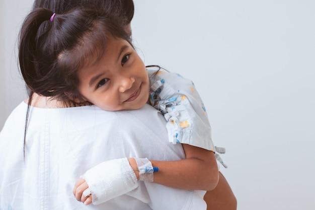 Niña asiática enferma que tiene una solución intravenosa vendada sonriendo y abrazando a su madre en el hospital Foto Premium